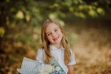 Portrait of cute blond school girl in white shirt holding ablue bouquet of flowers and smile. Back to school. Copy space