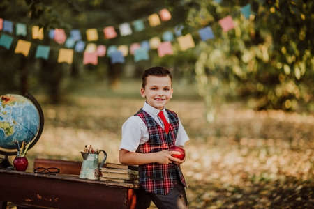Young boy in school uniform posing with newton apple near an old wooden desk in the park. Back to school. Flags background 스톡 콘텐츠