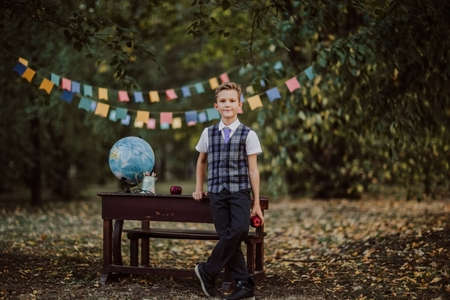 Young cute blond boy in school uniform posing near an old wooden desk in the park. Back to school. Flags background