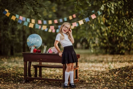 Young cute blond girl in school uniform and glasses posing near an old wooden desk in the park. Back to school. Flags background