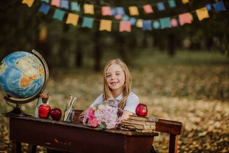 Young cute blond girl in school uniform posing sitting at an old wooden desk in the park. Back to school. Flags background
