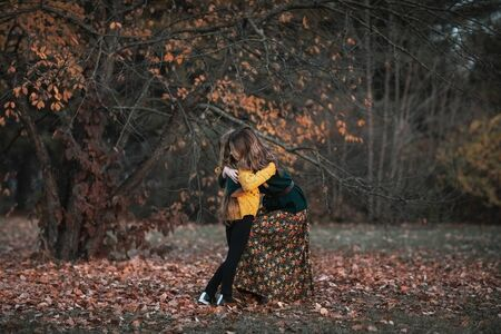 Young attractive woman in green sweater and long skirt and cute teen girl in yellow sweater with long blond hair spending time together in autumn park. Copy space.