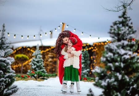 Young pretty long haired girl and beautiful brunette woman skating at the open skating rink. Christmas background.