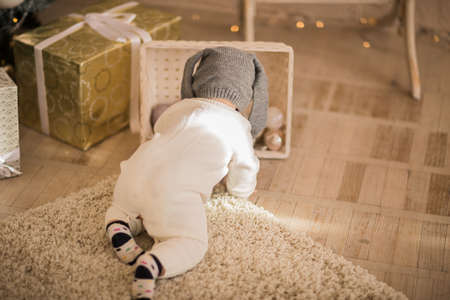 Baby in white winter body and rabbit hat crawling on the floor at white Christmas studio.