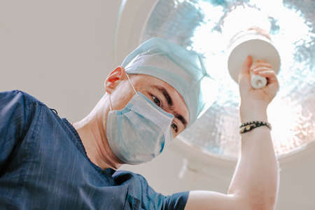 Portrait of a handsome male white doctor at medical mask and cap in blue smock posing against medical light in the operation room.