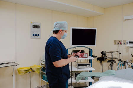 Adult male doctor at blue medical smock configuring medical equipments at the operation room. Copy space. Standard-Bild