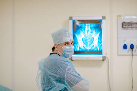 Adult white doctor posing near the x-rayed at the white operation room. Copy space.