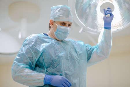 Adult doctor at medical mask, gloves and smock tasting light at the operation room. copy space. Standard-Bild