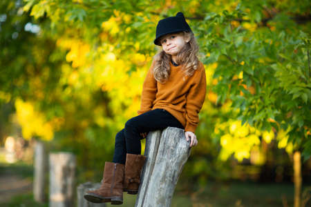 Young pretty girl in red sweater and boots, black pants and hat like a cat sitting up the wooden stump and smiling. Autumn background. Copy space.