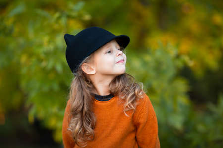 Portrait of young pretty girl with curly tails in red sweater and black hat like a cat. Autumn background. Copy space.