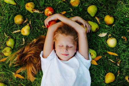 Young girl laying on green grass among pears, apples and small orange leaves.