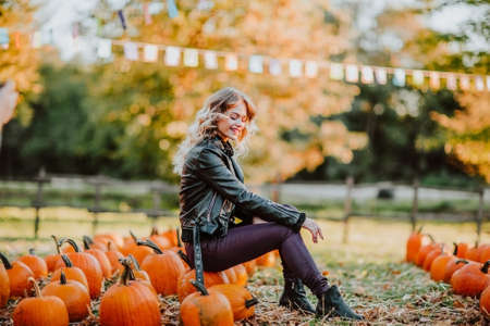 Beautiful young woman sitting on a pumpkins field. 스톡 콘텐츠
