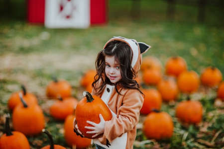 Young girl in red autumn jacket like a fox posing on  pumpkins field. 스톡 콘텐츠 - 155309349