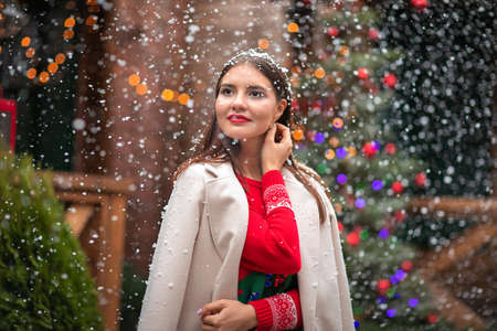 Portrait of pretty young asian brunette woman with red lips in red sweater and white coat posing under the heavy snowing. Christmas background.