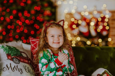 Pretty young girl in green Christmas pyjamas sitting on green sofa with Christmas pillows holding small white rat. Christmas background.