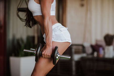 Sportswoman with long brunette hair in white shorts and crop top doing low body with bars at home's veranda. Archivio Fotografico