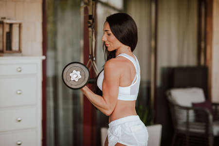 Young attractive sportswoman with long brunette hair in white shorts and crop top doing exercises at home's veranda. Archivio Fotografico