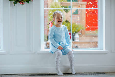 Young pretty girl in blue winter dress and tights sitting near the big window with Christmas background. Snowing.