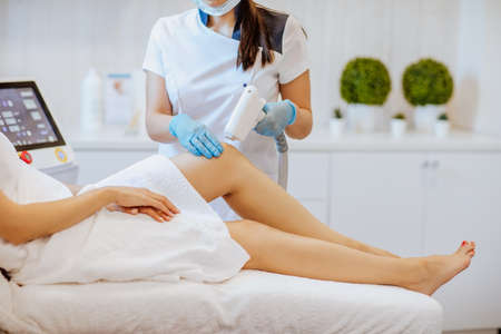 Doctors's hands in blue medical gloves holding a depilation machine and using it on the woman's legs. Focus is at the doctor's hands.Copy space.
