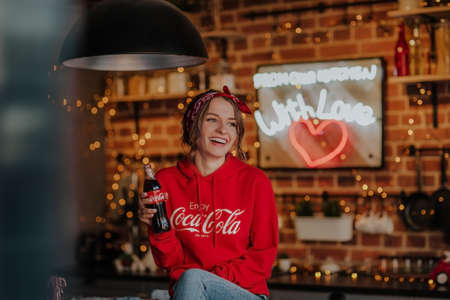 Woman in a hoodie with coca cola logo posing with bottle of coke in the kitchen. 에디토리얼