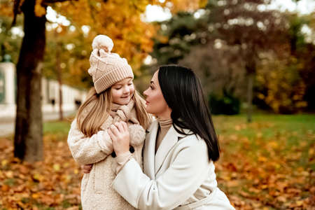 Mom brunette and blonde daughter in beige cap hold hands and look at each other in autumn park.