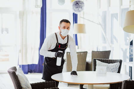 Male waiter in black apron, medical mask and gloves cleaning white table at the restaurant by disinfection bottle. 스톡 콘텐츠
