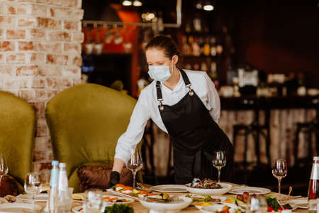 Young female waiter in uniform with medical mask and gloves serving in the restaurant. Copy space. 스톡 콘텐츠