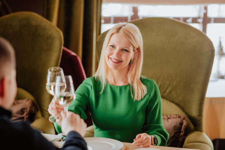 Young attractive blond woman in green dress spending time with man with glass of white wine in the restaurant. 스톡 콘텐츠