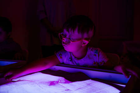 Child with Down syndrome is engaged in sand therapy on a light table with lights. High quality photo