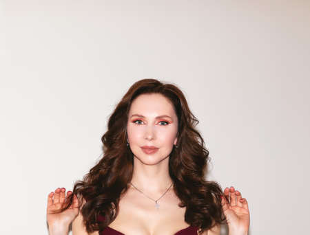 Attractive slim woman in wine dress with make up and curly long hair posing on white background. Copy space. 스톡 콘텐츠