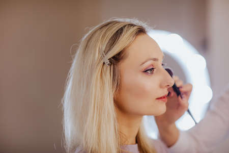 Woman's hand with brush making make up for a pretty blond female model. Copy space.