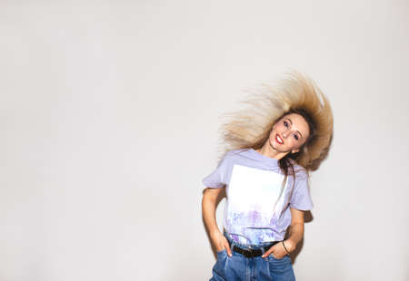 Beautiful blond woman in violet shirt with bright make up waving her hair near white wall. Copy space. 스톡 콘텐츠