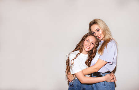 Portrait of pretty blond mother and cute teen girl with long curly hair posing near white wall. Copy space.