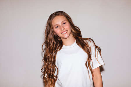 Portrait of beautiful teen girl in white shirt with long curly hair and make up posing near white wall with copy space.