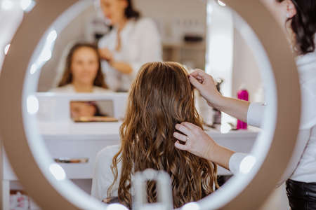 Curly hairdressing for long girl's hair. View from the back. Focus is at the hair. 스톡 콘텐츠