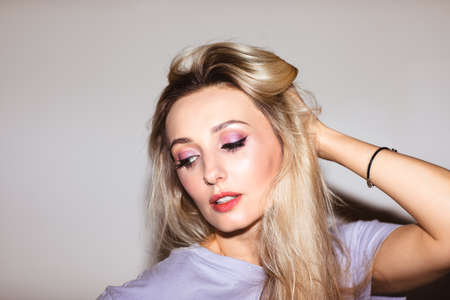 Beautiful blond woman in violet shirt with bright make up posing near white wall. Copy space.