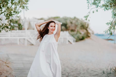 Young attractive brunette woman in white summer dress posing on a seacoast in hotel. Happiness. Copy space.