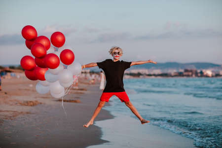 Blond cute teen boy with face painting like a clown in summer shorts and shirt posing with bunch of balloons on a sand beach. Copy space. 스톡 콘텐츠