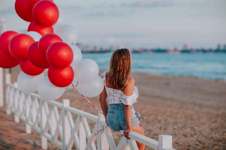 Pretty young woman in summer shorts and blouse sitting on white wooden fence on the sand beach holding bunch of balloons. Copy space.