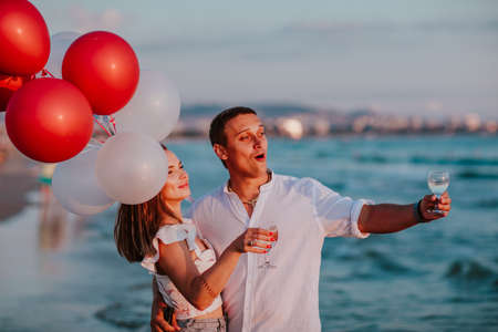 Young pretty woman and handsome man in white summer clothes hugging and celebrating together with champagne and balloons on a sea coast. Copy space.