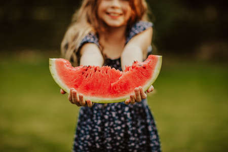 Funny young girl with long hair in blue summer dress posing with big slice of watermelon in the garden. Copy space. Focus is at the slice. 스톡 콘텐츠