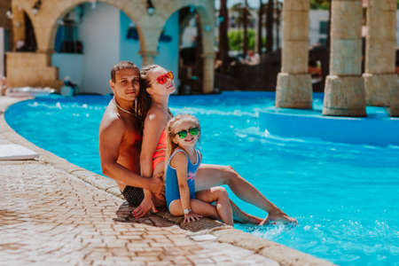 Happy family of three in summer bikini and glasses sitting near the pool in hotel. Copy space.