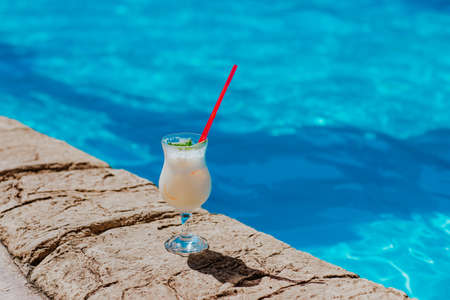 Glass of Pina colada cocktail standing near the pool in hotel. Copy space. 스톡 콘텐츠