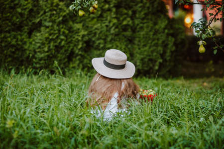Young girl with long hair in summer hat and white overalls sitting by her back in the grass with a harvest in her garden. Copy space.