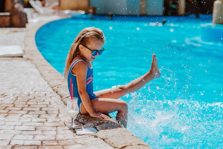 Young pretty girl in blue bikini and sun glasses sitting near the pool with cocktail and smiling. Copy space.