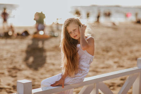 Pretty young girl with long blond hair in white summer overalls sitting on white hotel fence holding the seashell. Copy space. 스톡 콘텐츠