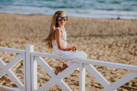 Pretty young girl with long blond hair in white summer overalls and sun glasses sitting on white hotel fence holding the seashell. Copy space. 스톡 콘텐츠