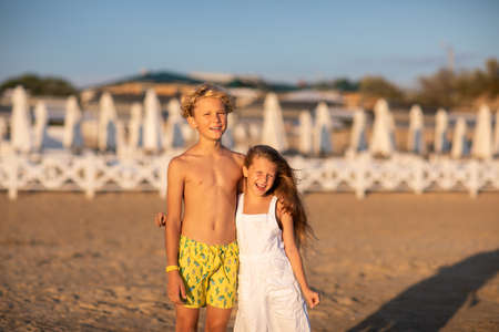 Young cute blond boy and girl posing on the sand beach against the hotel while sunset. Copy space.