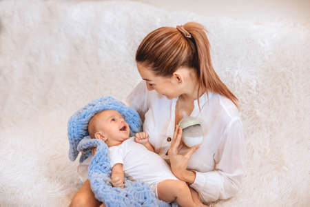 Beautiful young mother with tail in white shirt smiling to her newborn baby and holding the bottle of milk. Copy space. Focus is at the baby. 스톡 콘텐츠