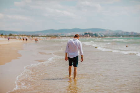 Man in white summer shirt and shorts walking along on a sand beach looking at water. View from the back. Copy space. Anapa city beach. Russia. 1 of august 2020.